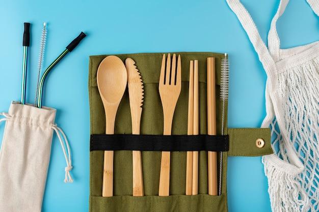 Zéro déchet un ensemble de couverts en bois, bambou, fourchettes, couteau, pailles en bambou. réduction du gaspillage. utilisation réutilisable.