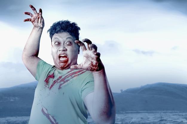 Zombie effrayant avec du sang et une blessure sur son corps marchant sur le terrain