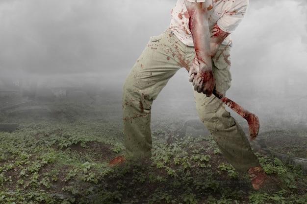 Zombie effrayant avec du sang et une blessure sur son corps tenant une faucille debout sur le cimetière