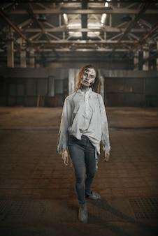 Zombie femelle marchant dans une usine abandonnée, horreur