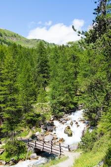 Zone de bardonecchia, région du piémont, alpes italiennes. pont sur la rivière dans la forêt alpine.