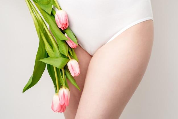 Zone de bikini d'une jeune femme portant un sous-vêtement blanc avec des tulipes roses sur fond blanc