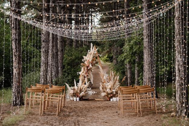 Zone de cérémonie de mariage avec des fleurs séchées dans un pré dans une forêt de pins bruns