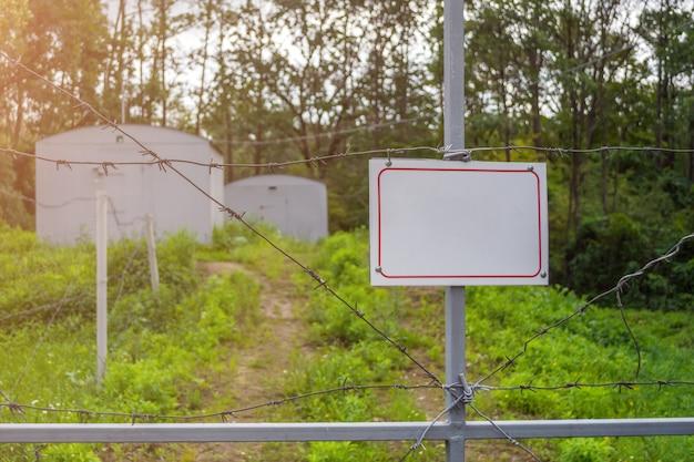 Zone interdite clôturée avec une clôture de barbelés. portail avec cadenas fermé à la clé