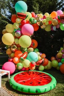 Zone photo avec des éléments gonflables lumineux sous la forme de différents fruits