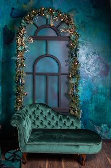 Zone photo de noël avec de l'or, des boules bleues et de l'épinette sur la fenêtre, canapé vintage en velours bleu.
