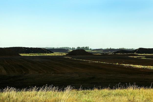 Une zone de production de tourbe noire, de montagnes de tourbe