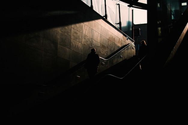 Zone souterraine sombre avec deux personnes descendant les escaliers