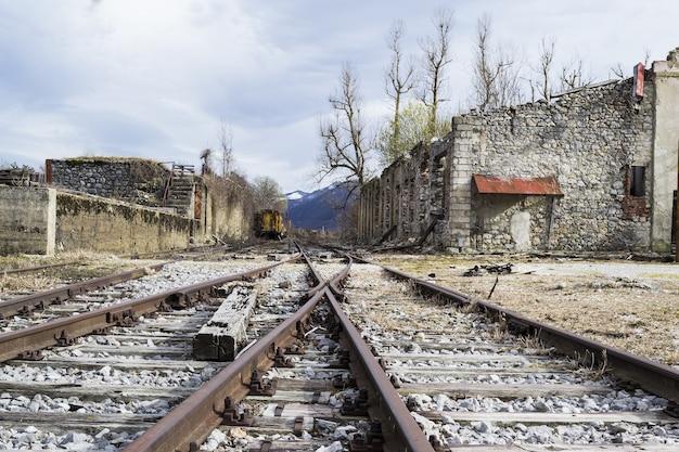 Zone avec des voies ferrées entourées de vieux bâtiments en béton sous un ciel nuageux