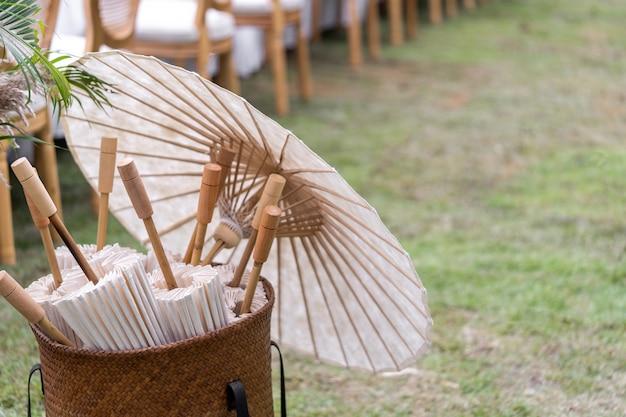 Zones de papier artisanal traditionnel dans un panier avec des parapluies dans la rue.