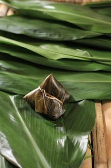 Zongzi ou bakcang, boulettes de riz gluant salées chinoises dans un emballage de feuilles de bambou. concept frais avec des feuilles fraîches de bakcang. copier l'espace pour le texte