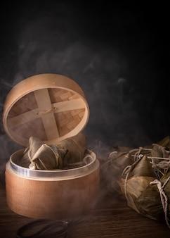 Zongzi, boulettes de riz cuites à la vapeur dans un bateau à vapeur sur une table en bois, célèbre nourriture savoureuse dans le concept de design de duanwu festival de bateaux-dragons, gros plan, espace de copie.