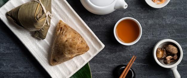 Zongzi. concept de design de vue de dessus de boulettes de riz pour le festival traditionnel chinois des bateaux-dragons (festival de duanwu) sur fond d'ardoise noire foncée.