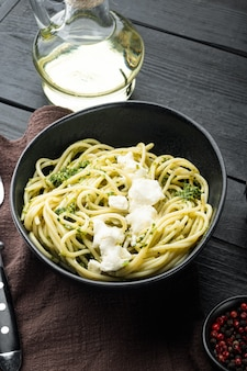Zoodles végétaliens avec jeu de pesto vert, dans un bol, sur une table en bois noir