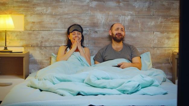 Zoom avant sur un beau jeune couple en pyjama riant en regardant la télévision la nuit.