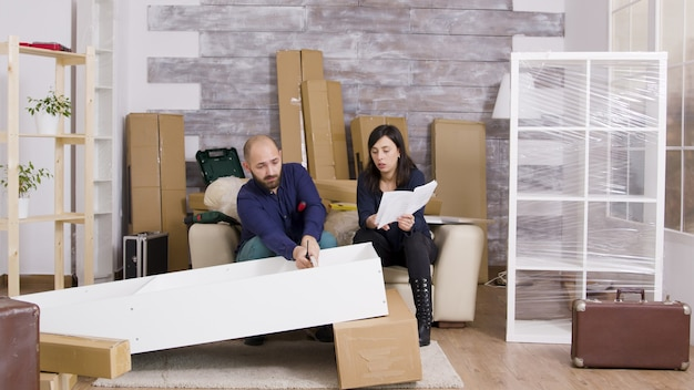 Zoom avant sur un jeune couple assemblant des meubles dans un nouvel appartement. couple utilisant des instructions pour assembler des meubles.
