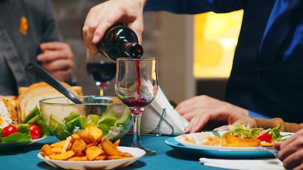 Zoom avant sur un jeune homme versant du vin rouge dans un verre lors d'un dîner en famille.