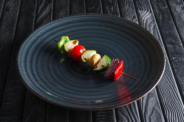Zuccini, poivrons, champignons, tomates et oignons grillés sur brochette