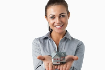 Agent immobilier tenant une maison miniature dans ses mains