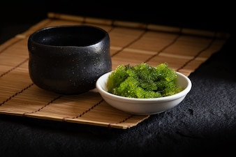Algues de raisins de mer ovales, gros plan Caviar vert sur fond sombre