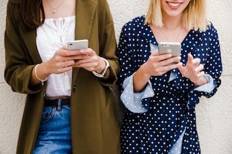 Amies s'appuyant sur le mur en utilisant un smartphone