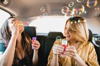Amies soufflant des bulles dans le véhicule