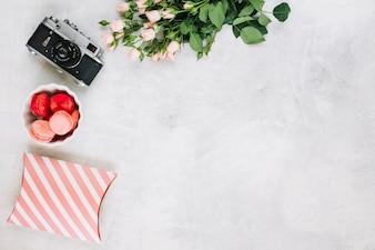 Appareil photo et macarons entre bouquet et boite