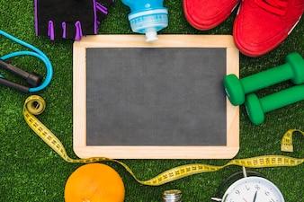 Ardoise en bois blanche avec corde à sauter; mètre ruban; Orange; alarme; des haltères; chaussures de sport; bouteille d'eau et des gants sur le gazon