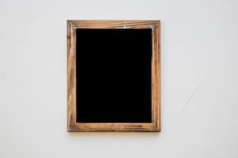 Ardoise vierge en bois sur un mur blanc