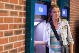 Assez content étudiant retirer de l'argent en souriant à la caméra