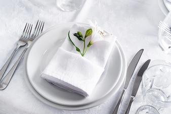 Assiette à table avec verre sur blanc