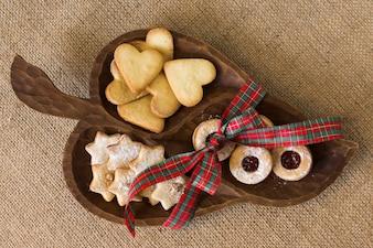 Assiette en bois avec différents biscuits sur la table