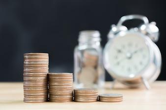 Augmenter la pile de pièces augmenter l'argent avec l'horloge floue et le fond de pot