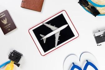 Avion sur tablette entouré d'accessoires de voyage