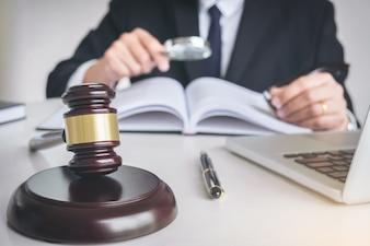 Avocat ou juge travaillant avec des livres de droit, signalez le cas sur une table dans un bureau moderne