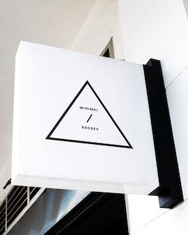 Badge triangulaire minimal sur une maquette de panneau blanc