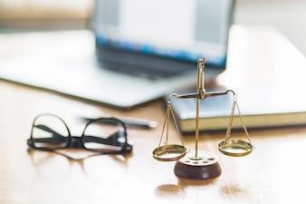 Balance de justice et lunettes sur un bureau en bois dans la salle d'audience