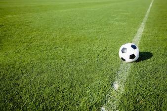 Ballon de football sur la ligne blanche