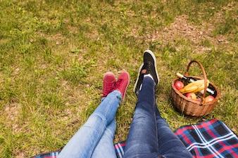 Basse section de la jambe du couple sur l'herbe verte avec panier pique-nique
