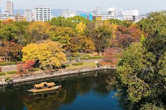 Bateau touristique naviguant autour du château d'Osaka avec des couleurs de feuillage d'automne, Japon