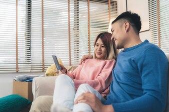 Beau couple asiatique attrayant avec tablette en position allongée sur le canapé pour se détendre dans leur salon