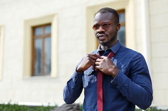 Bel homme afro-américain fixe sa cravate rouge sur la chemise bleue debout à l'extérieur