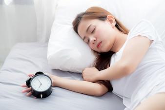 Belle femme asiatique éteindre réveil bonjour.