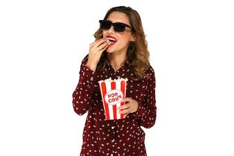 Belle femme en lunettes 3d, manger du pop-corn de seau avec du maïs soufflé