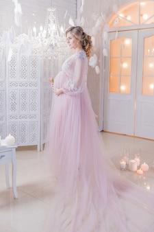 Belle femme enceinte en robe rose riche tient les mains sur son ventre posant