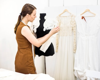 Belle jeune designer travaillant sur la robe en magasin