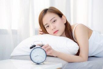 Belle jeune femme asiatique éteint réveil le matin.