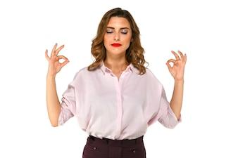 Belle jeune femme d'affaires médite, en essayant de se calmer après le travail