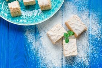 Biscuit gâteau tarte aux pommes candy pastila décorée de feuilles de menthe sur planche à découper en bois bleu