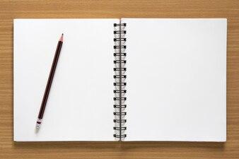 Bloc-notes en spirale vierge et crayon sur fond de bois